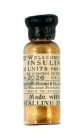 Bottle of insulin with green label printed in black and black rubber stopper