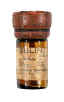 Bottle of insulin with with beige label printed in black and red rubber stopper