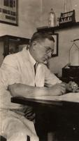 Photograph of F. G. Banting writing at his desk ca. 1926