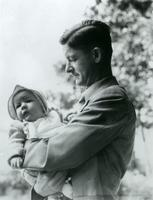Photograph of Jim Havens holding one of his children